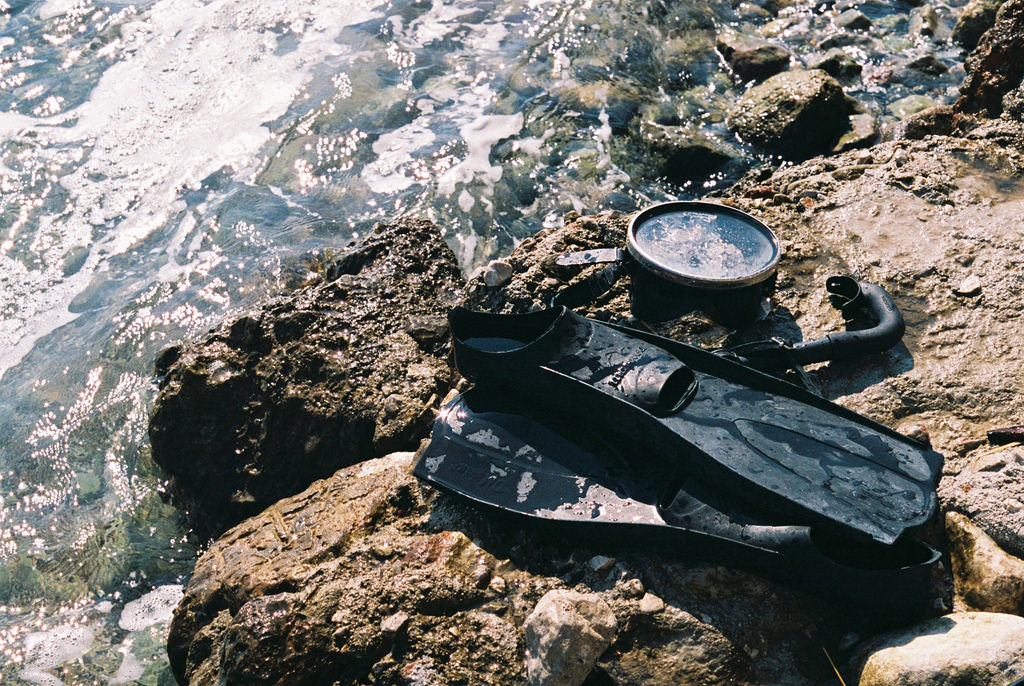 Flippers, mask and snorkel on rocks by sea